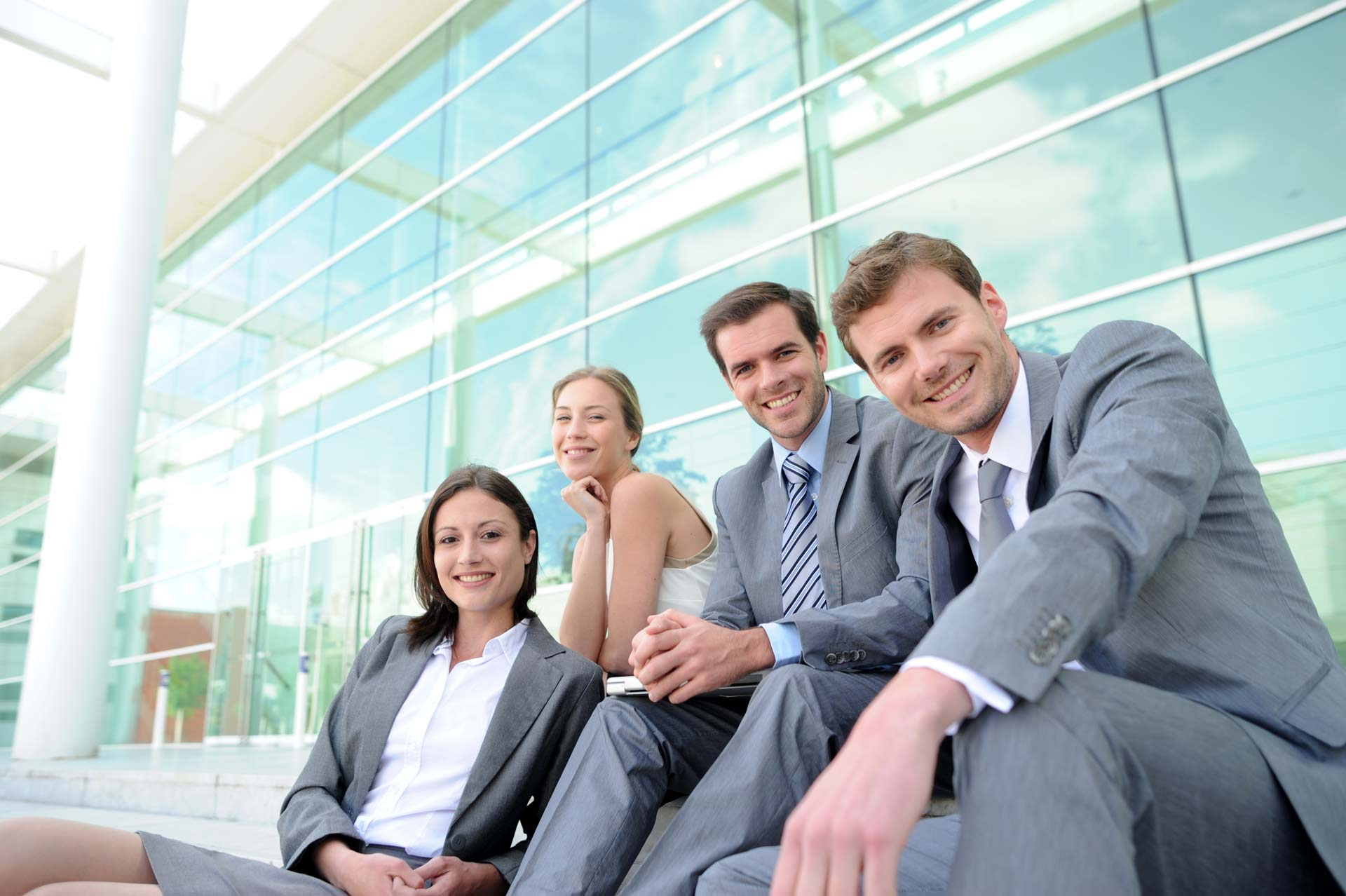 4 business professionals sitting outside during the day smiling at the camera
